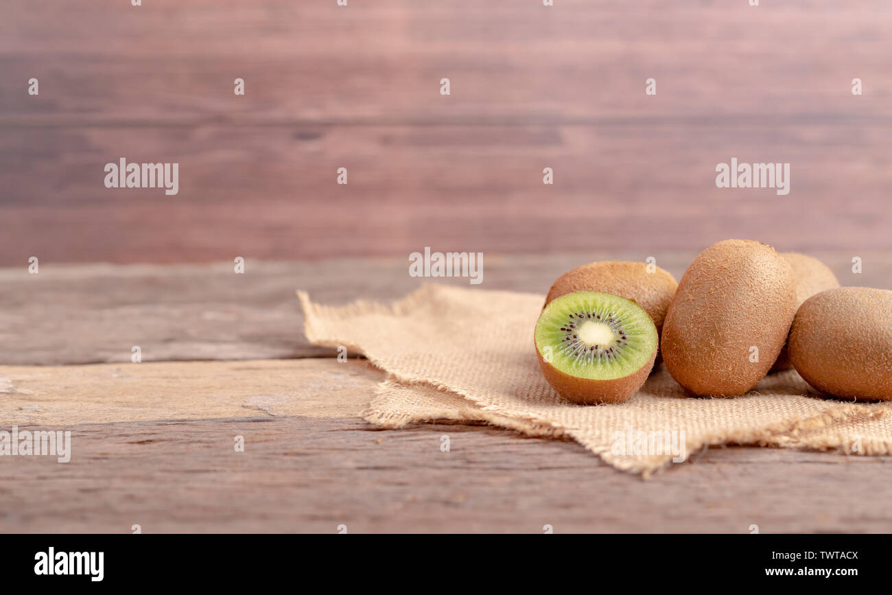 Kiwi fruits (Actinidia chinensis) and a half on the sack place on the wooden table. - Stock Image