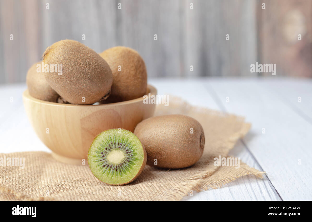 Kiwi fruits in a bowl, a half on the sack place on the wooden table with copy space. - Stock Image
