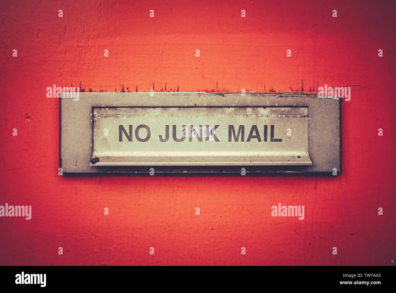 A Letterbox On A Grungy Orange Door With A No Junk Mail Sign Stock Photo