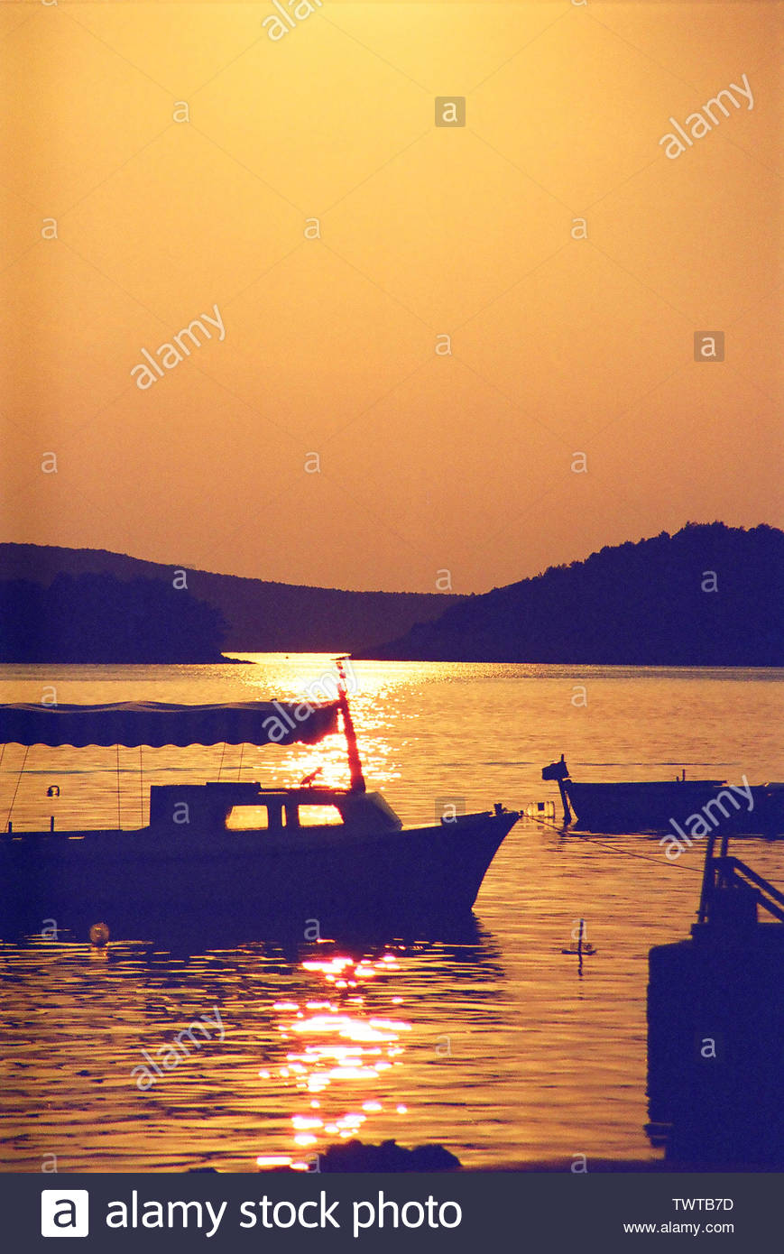 spectacular sunset among the fishing boats of Dubrovnik with red and yellow reflections on the sea - Stock Image