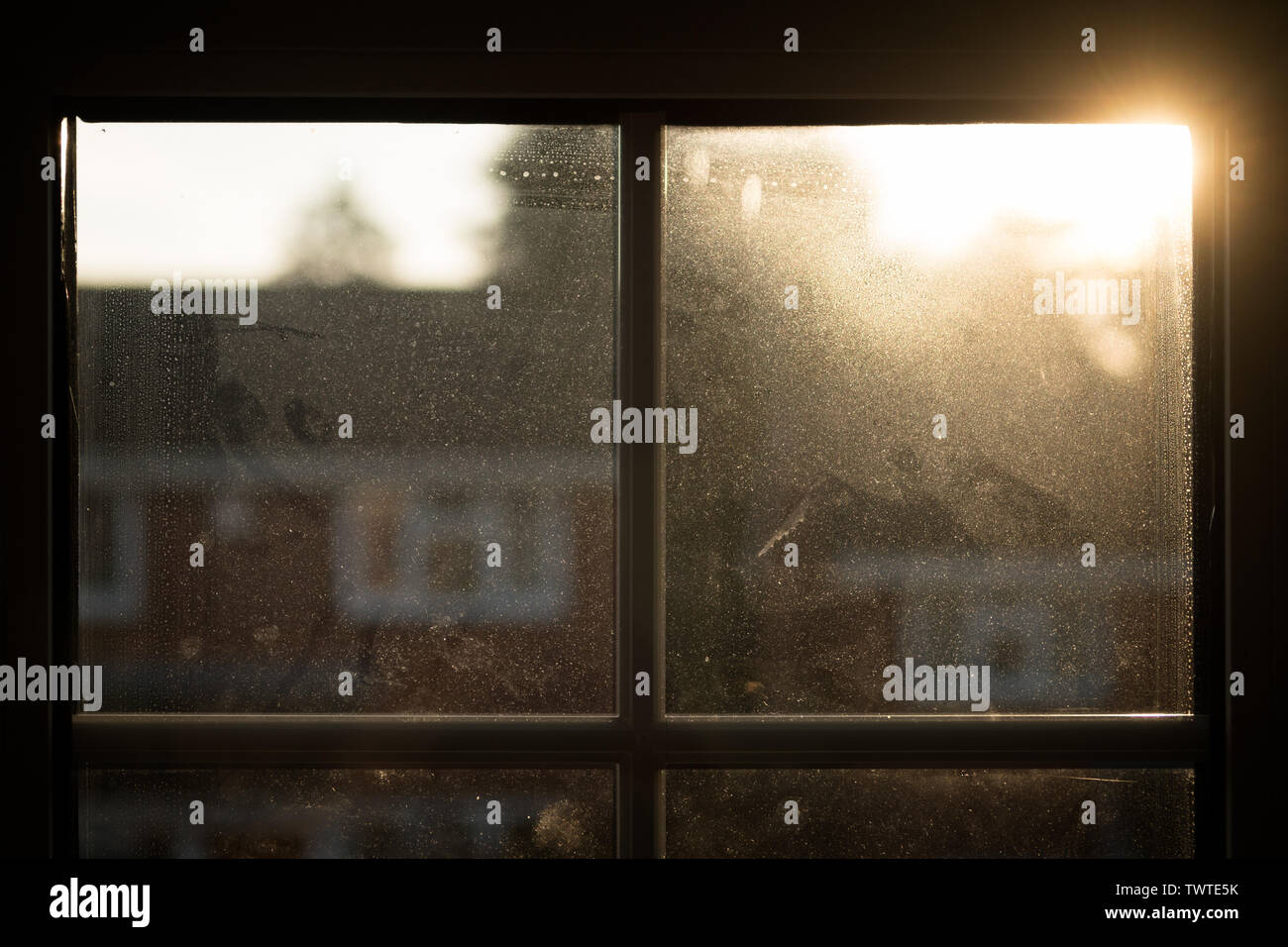 Sun rising over rooftop, seen through house window misted by dust and condensation; landscape format. - Stock Image