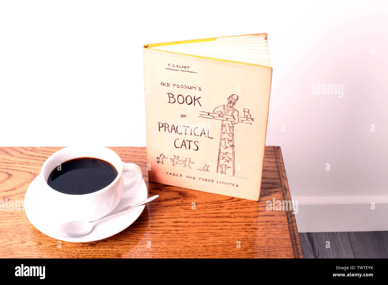 Old Possums Book of Practical Cats - A book of poems by T.S. Eliot with a cup of black coffee on a wooden coffee table with white background - Stock Image