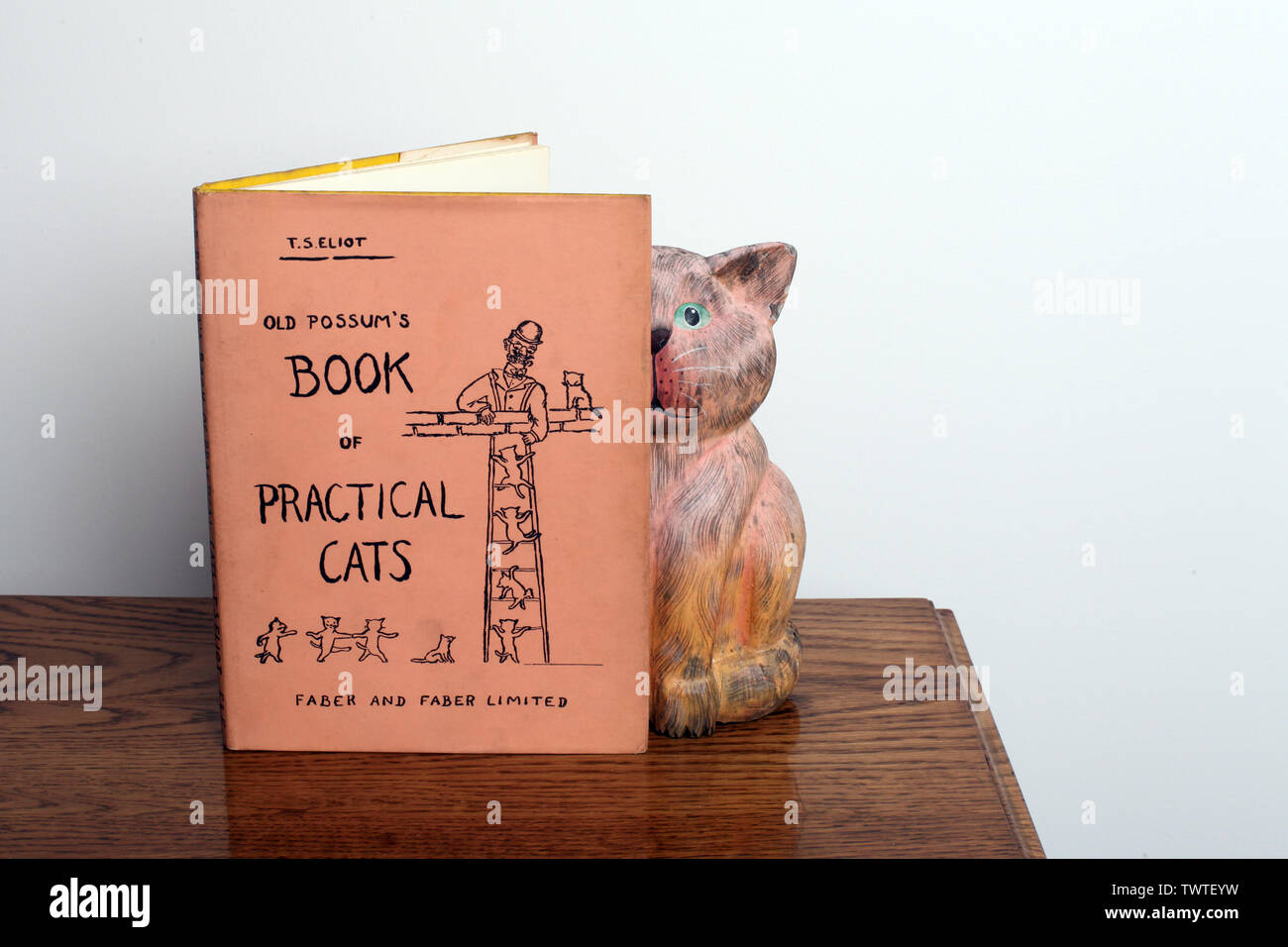 Old Possums Book of Practical Cats - A book of poems by T.S. Eliot with statue of a curious cat on a wooden coffee table - Stock Image