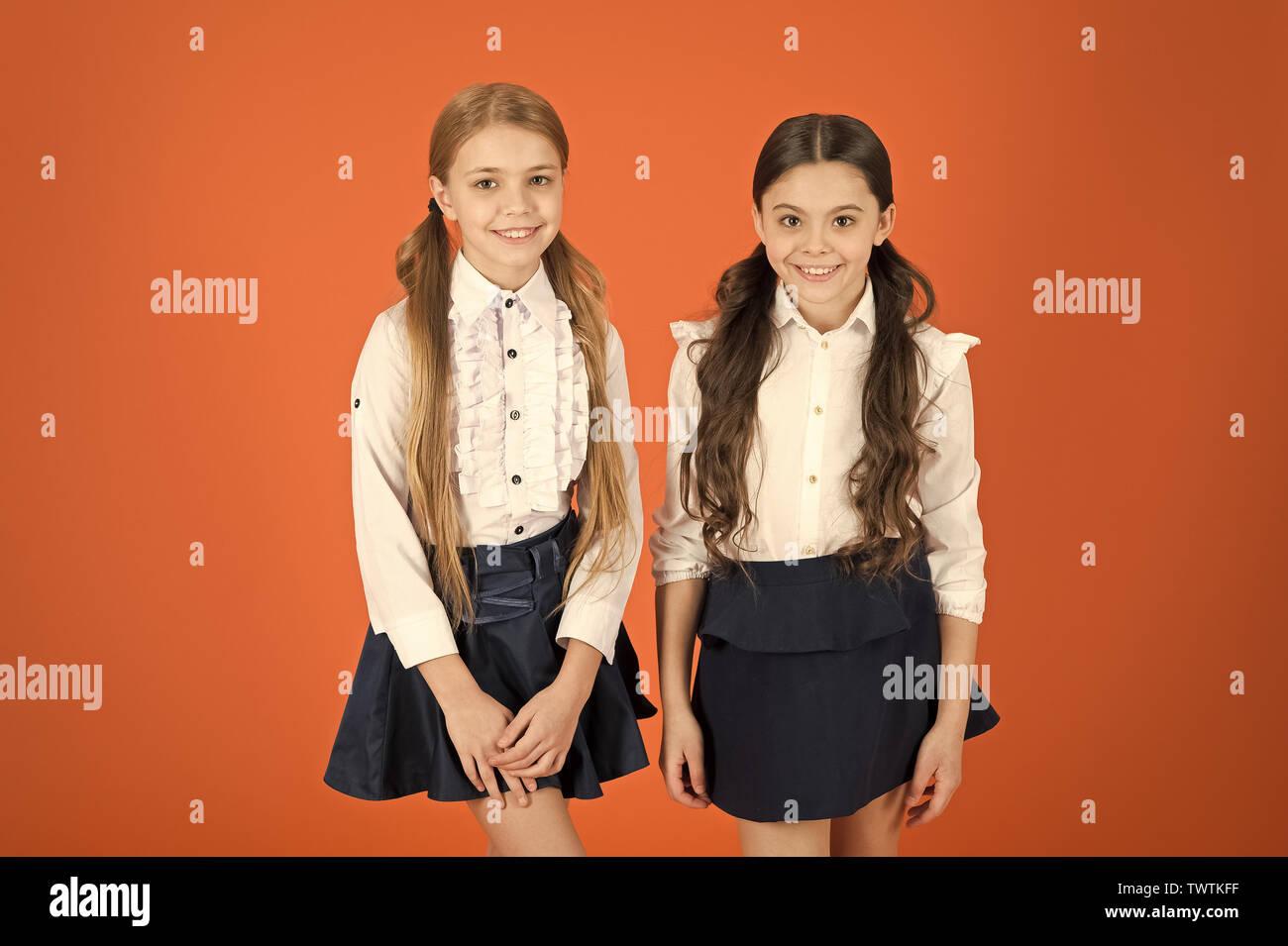 Keeping the look totally trendy. Cute schoolgirls. School children