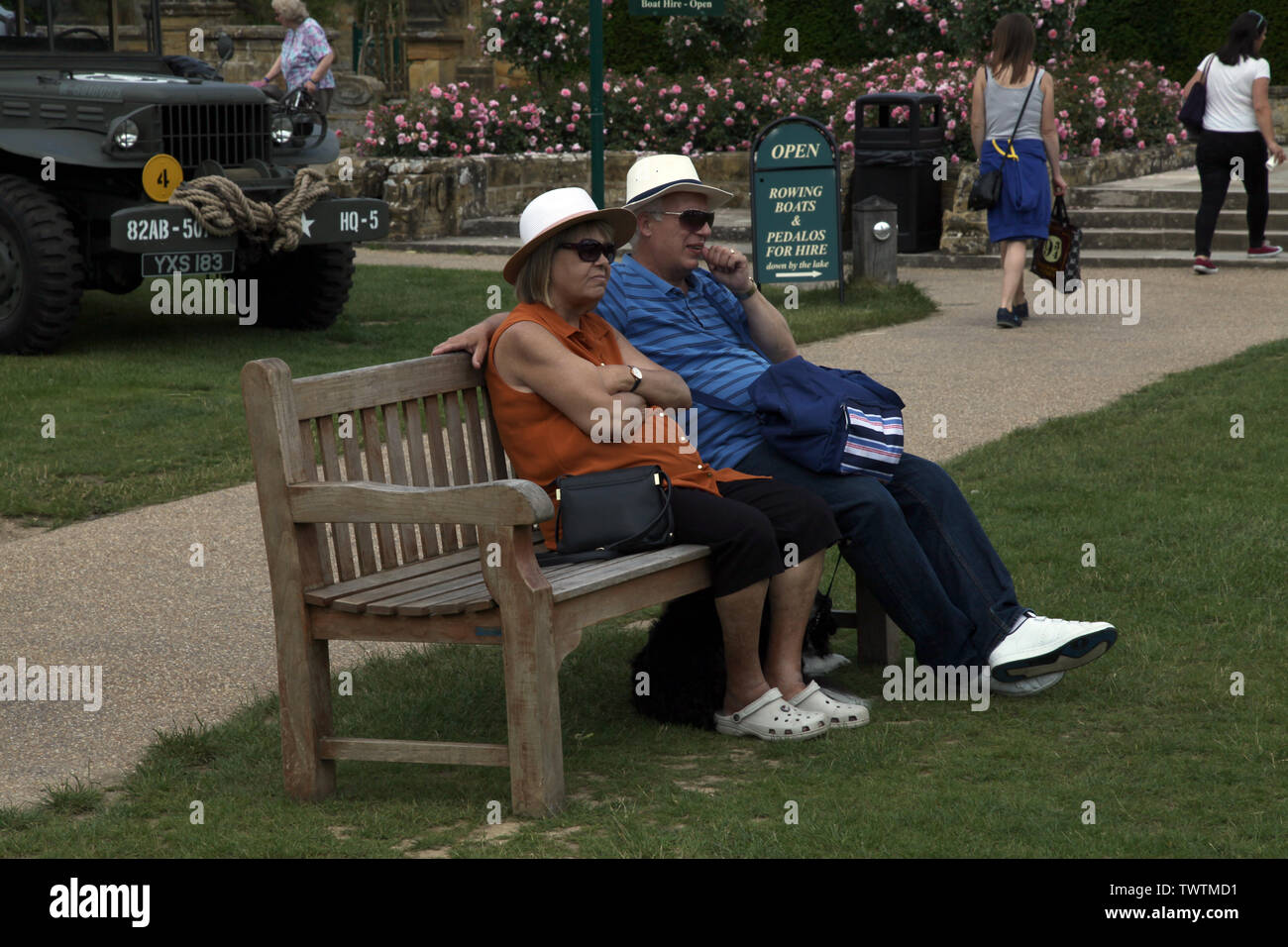 Edenbridge, Kent, UK - Older couple sitting outside on a bench watching the world go by in daytime on a sunny day Stock Photo