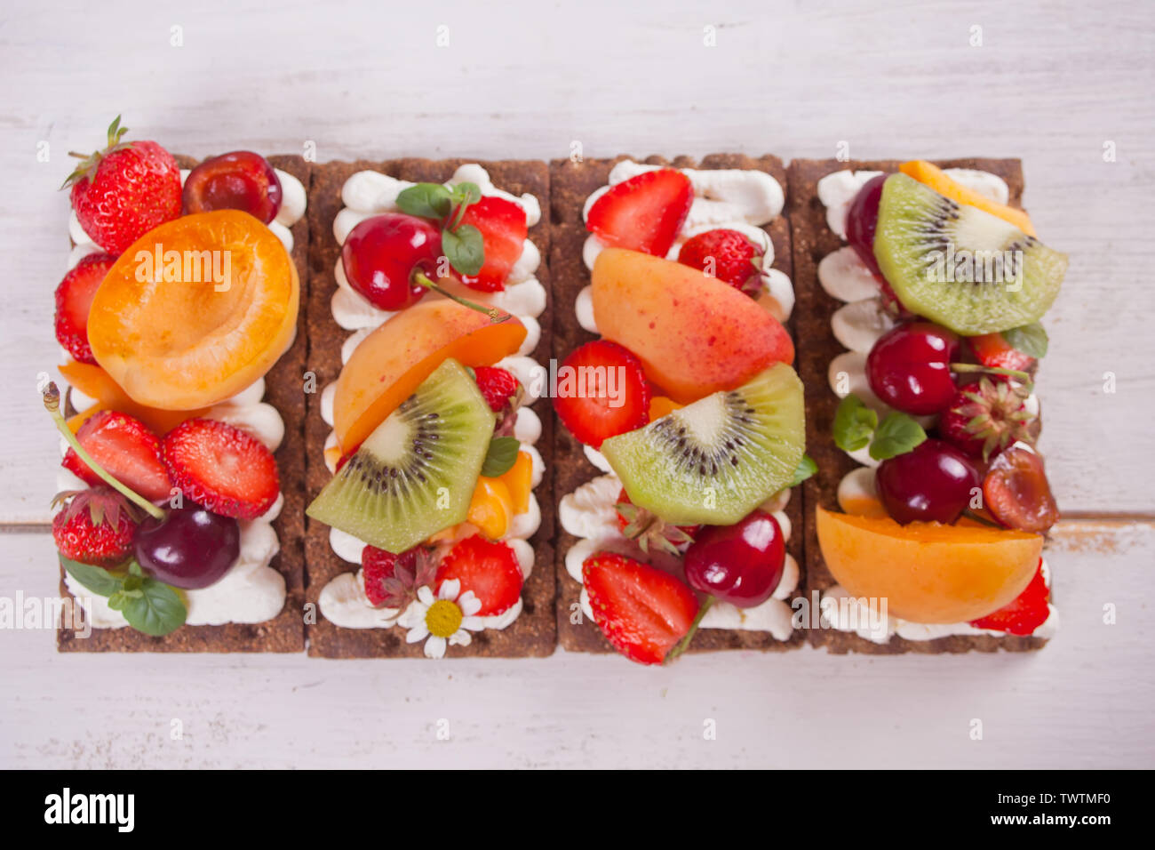 Crisp fitness health bread with creme cheese, fruit and berries on the white wooden background. Top view. - Stock Image