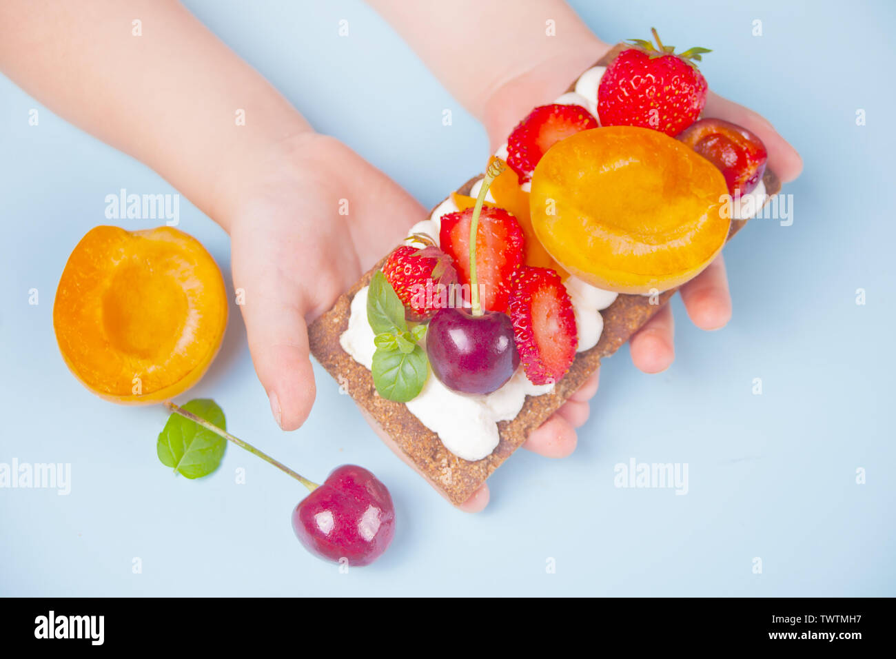 Child hands put crisp fitness health bread with creme cheese, fruit and berries on the blue background. Top view. - Stock Image