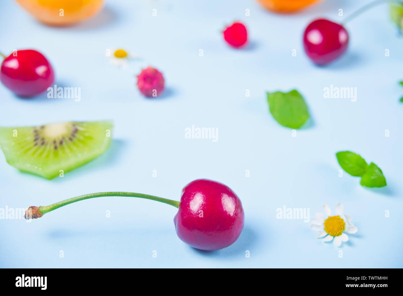 Scattered cherry berries, kiwi, strawberries, mint leaves on the blue background. - Stock Image