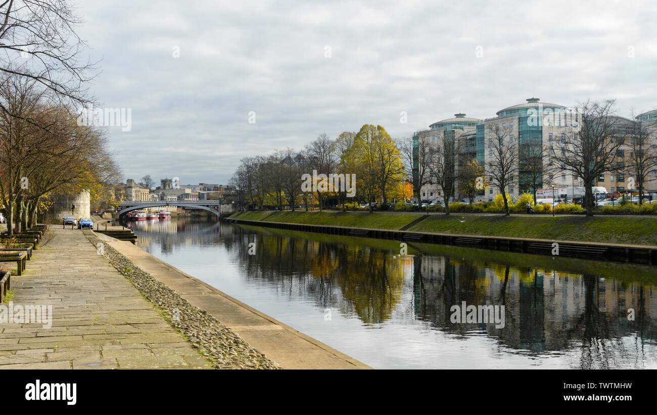 Beautiful quiet riverside setting by Lendal Bridge, buildings clearly reflected in flowing water of River Ouse - York, North Yorkshire, England, UK. - Stock Image