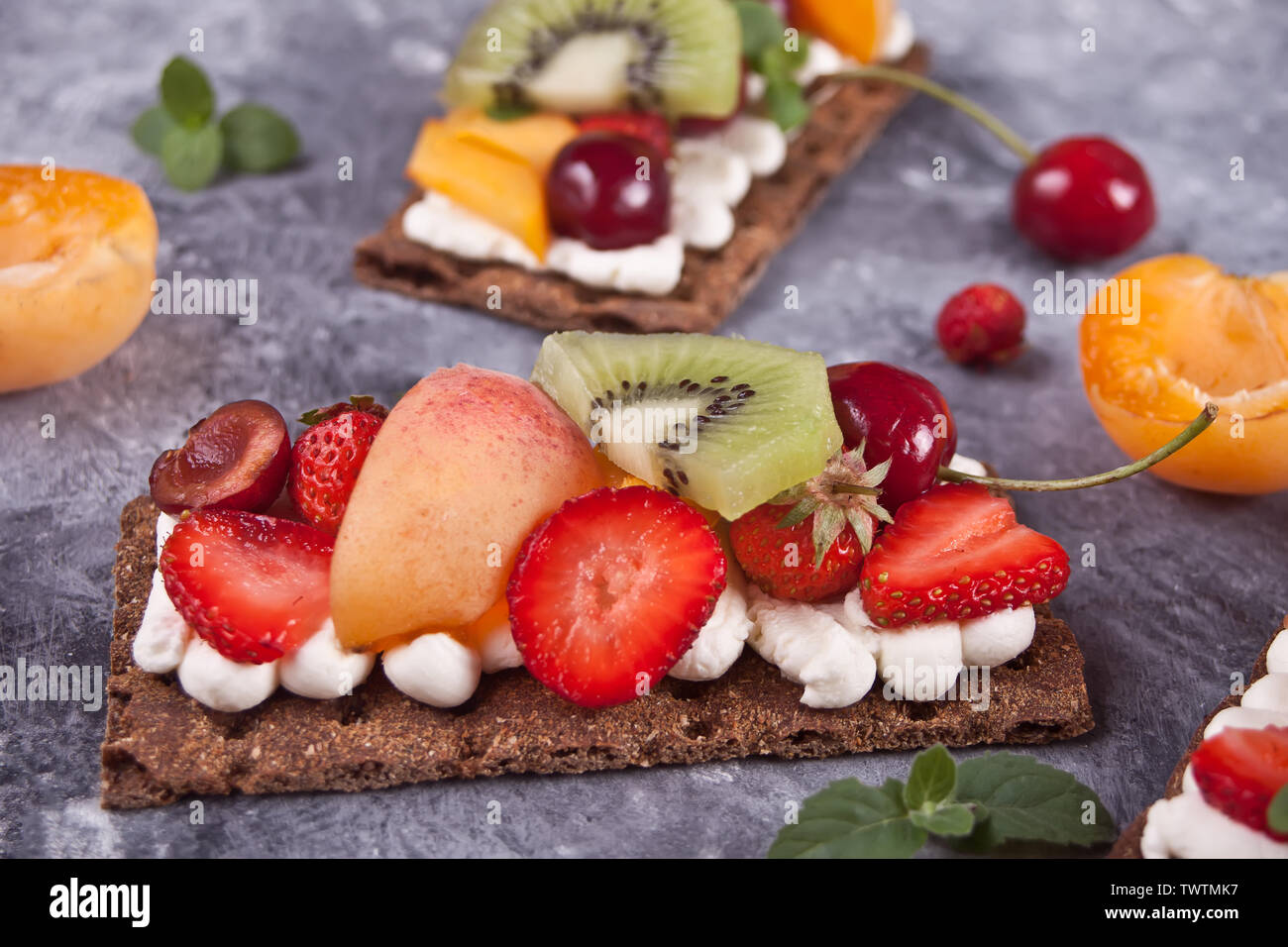 Crisp fitness health bread with creme cheese, fruit and berries on the gray concrete background. - Stock Image