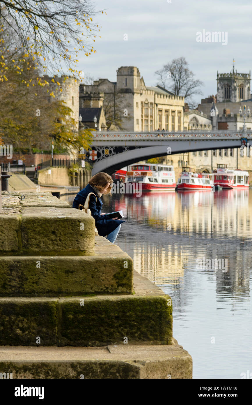 Quiet scenic riverside setting by Lendal Bridge (boats reflected in River Ouse & woman reading on riverbank) - York, North Yorkshire, England, UK. - Stock Image