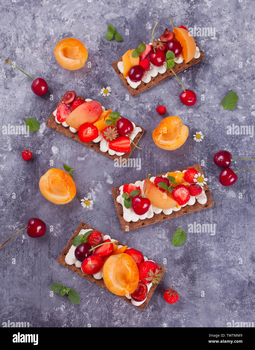 Crisp fitness health bread with creme cheese, fruit and berries on the gray concrete background. Top view. - Stock Image