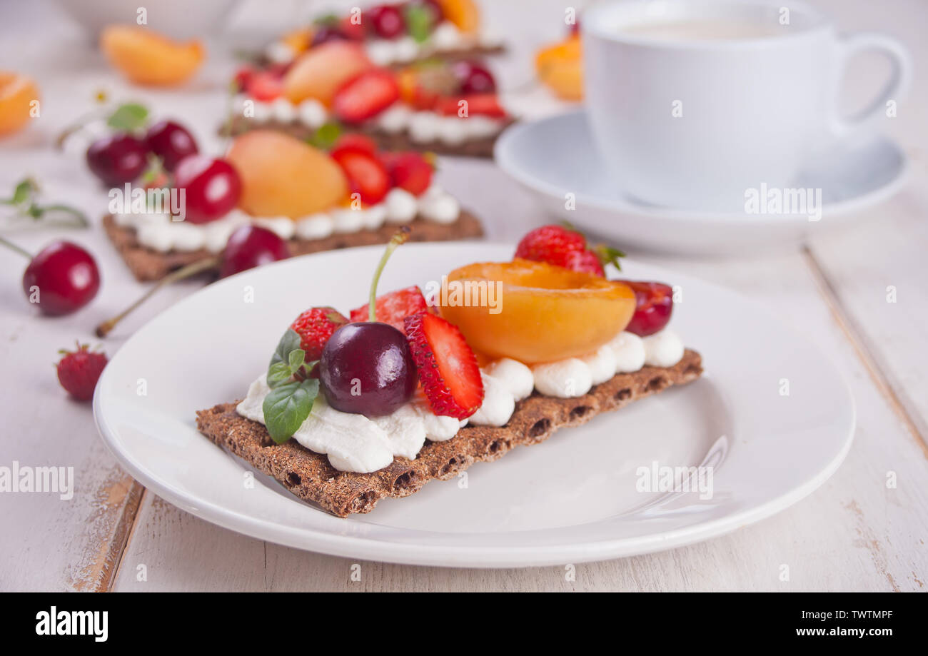 Crisp fitness health bread with creme cheese, fruit and berries and cup of tea on the white plate on the white wooden background. - Stock Image
