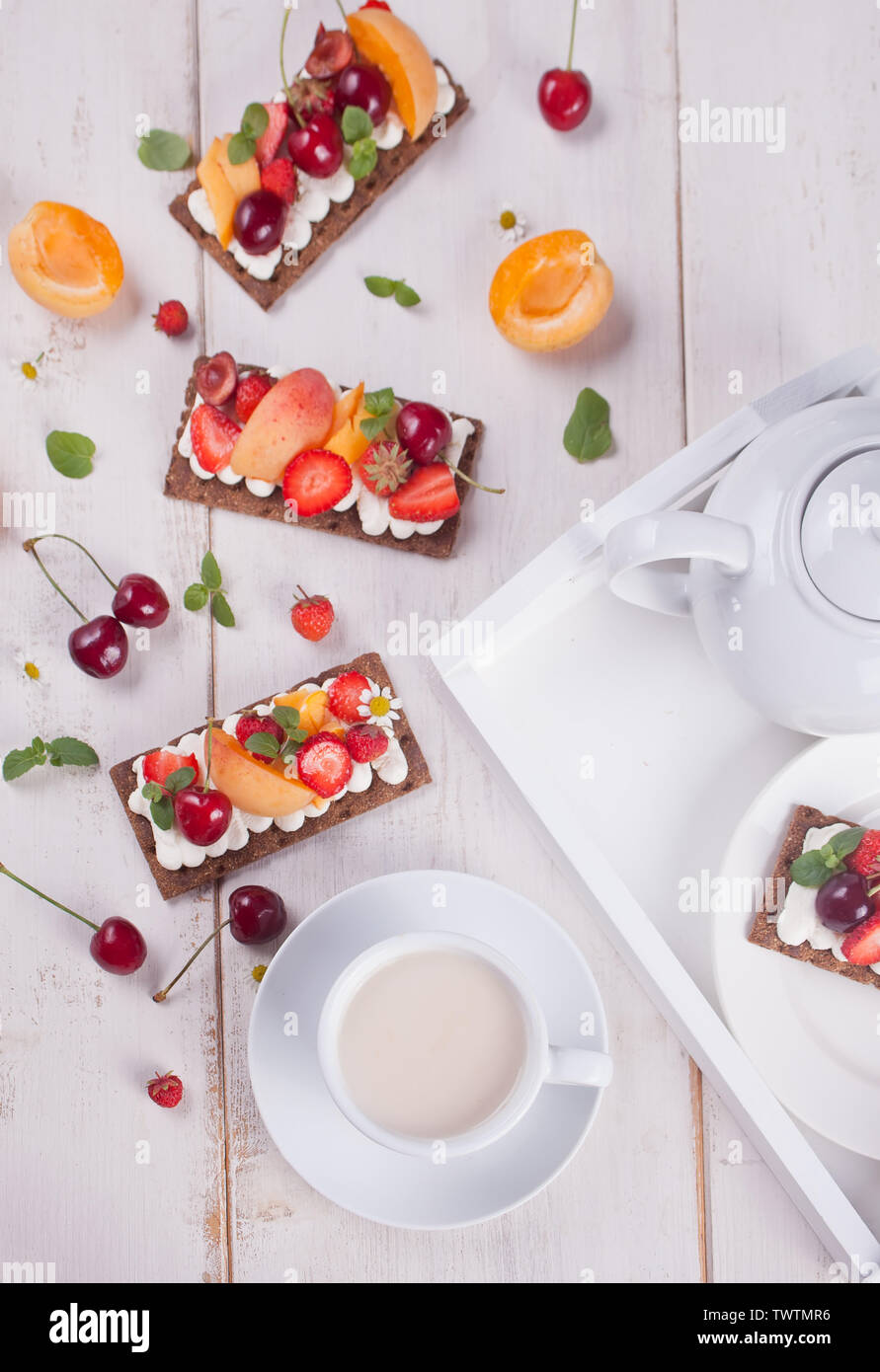Crisp fitness health bread with creme cheese, fruit and berries and cup of tea on the white plate on the white wooden background. Top view. - Stock Image