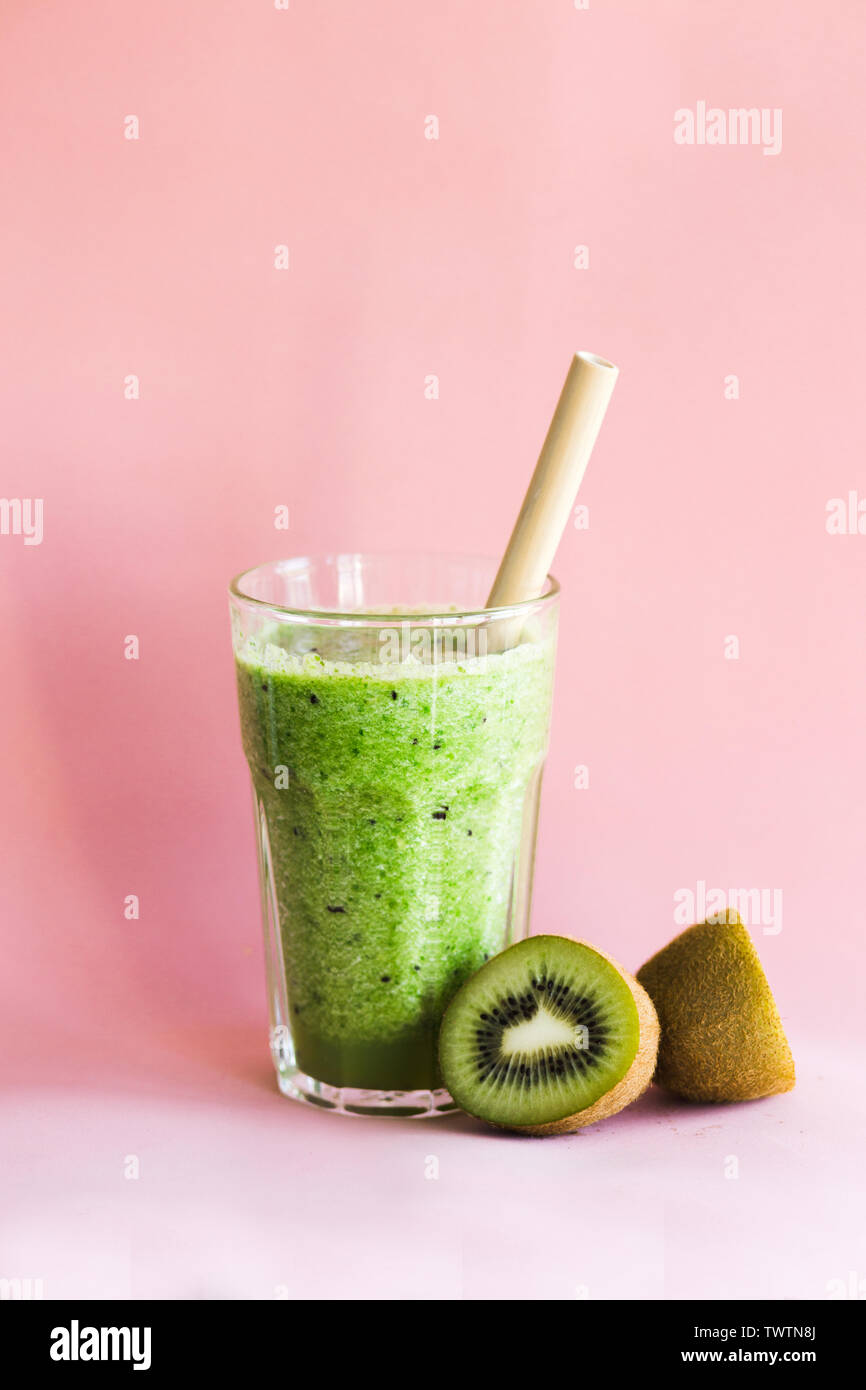 Healthy green smoothie with kiwi and spinach in a glass Cup on a pink background - Stock Image