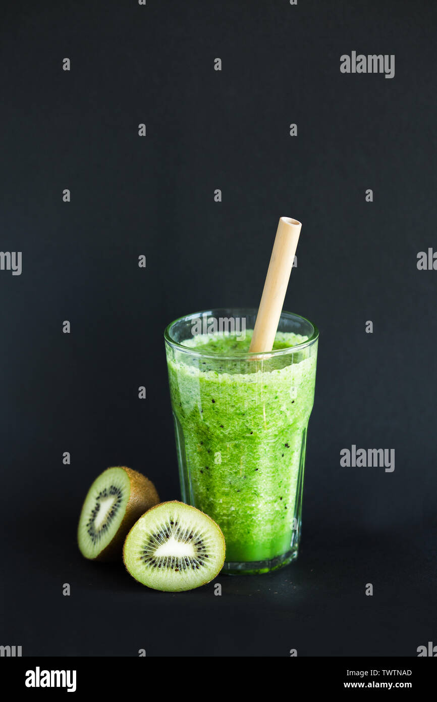 Healthy green smoothie with kiwi and spinach in a glass Cup on a black background - Stock Image