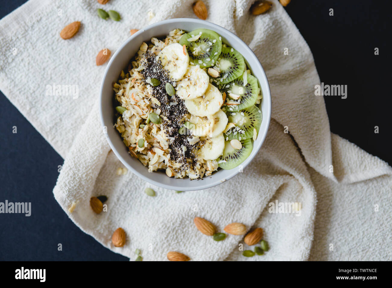 healthy Breakfast of oatmeal with kiwi, banana and chia seed on a white napkin, on black background - Stock Image