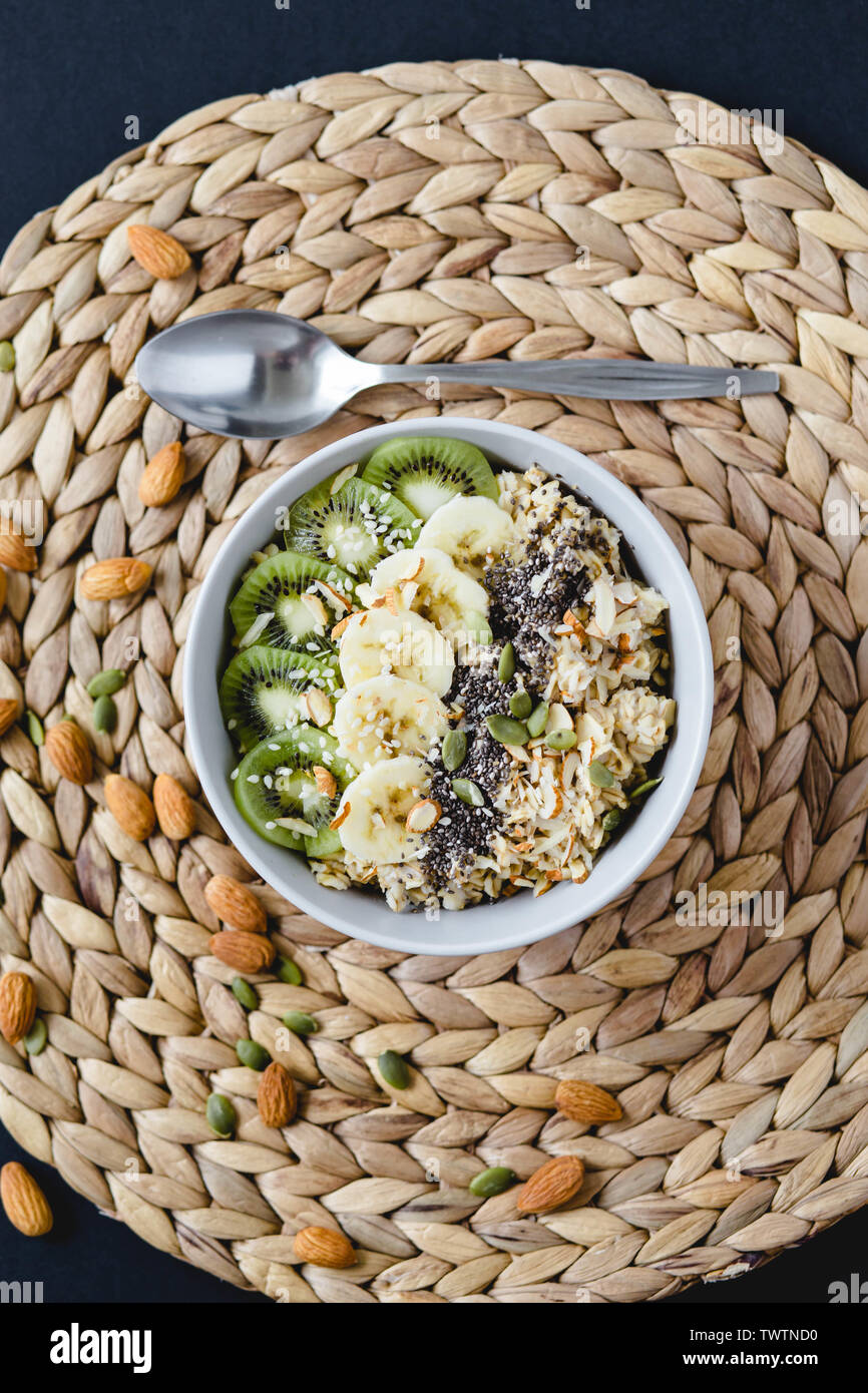 healthy Breakfast of oatmeal with kiwi, banana and chia seed on a wicker napkin, on black background - Stock Image