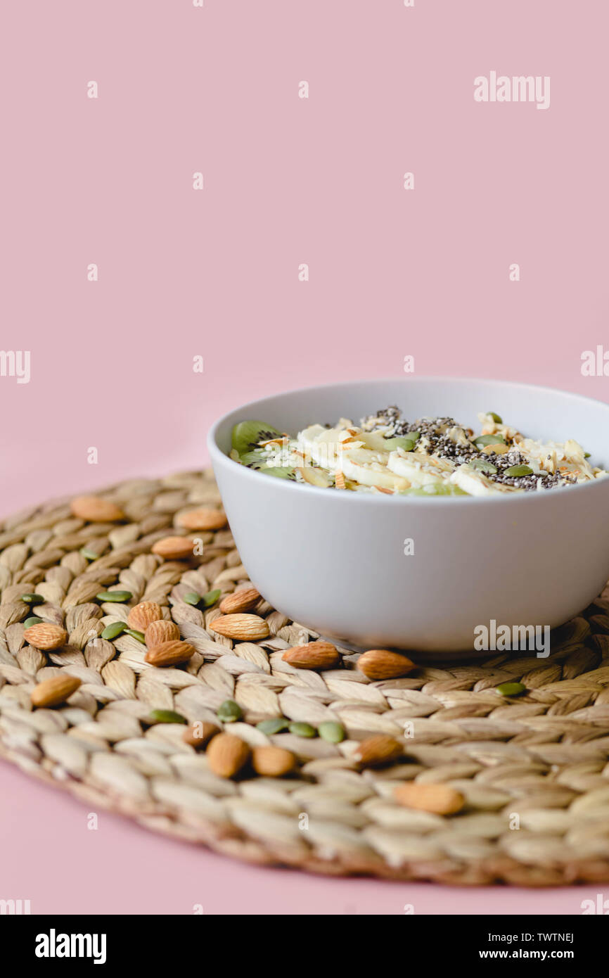 healthy Breakfast of oatmeal with kiwi, banana and chia seed on a white napkin, on pink background - Stock Image