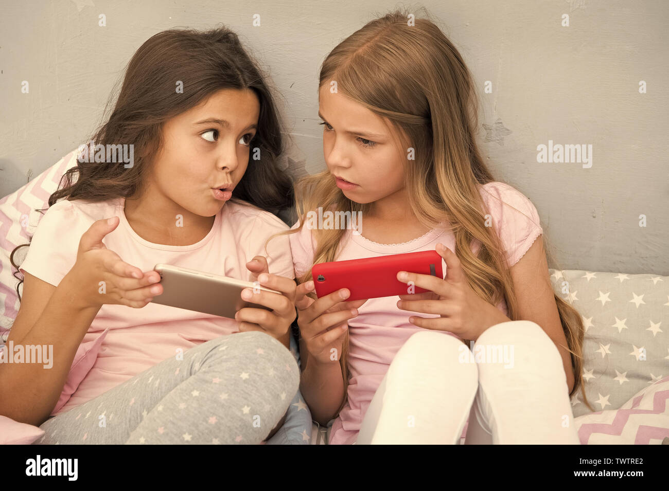 Kids play smartphone mobile game application. Smartphone application concept. Girlish leisure pajama party. Girls smartphone little bloggers. Explore social network. Smartphone for entertainment. Stock Photo