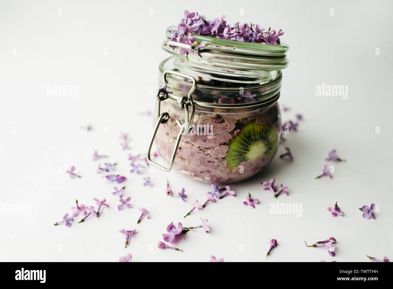 healthy smoothie breakfast in a glass jar with lilac flowers on white background - Stock Image