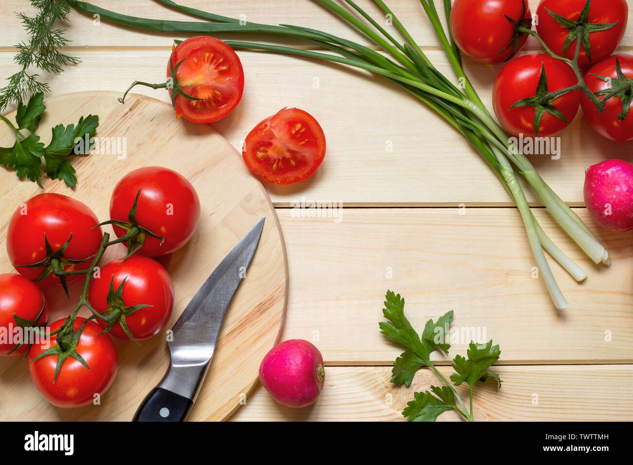 Healthy food cooking concept. Fresh tomatoes on branch, radish, onion, dill and parsley laid out on rustic light wooden table. Knife on kitchen board. Stock Photo