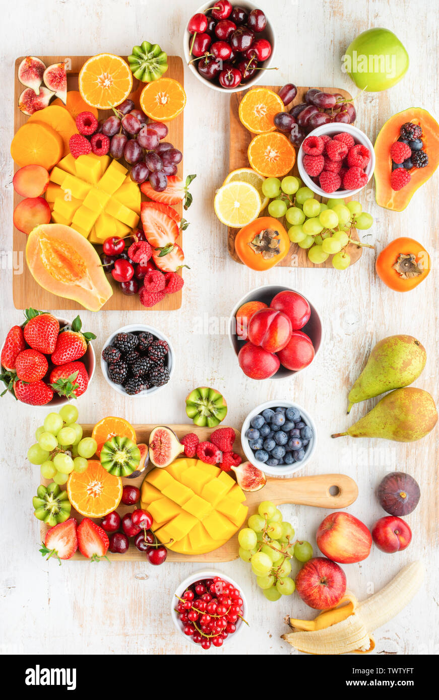Vegan breakfast, cut colorful rainbow fruits, strawberries raspberries oranges plums apples kiwis grapes blueberries mango persimmon, copy space, sele - Stock Image
