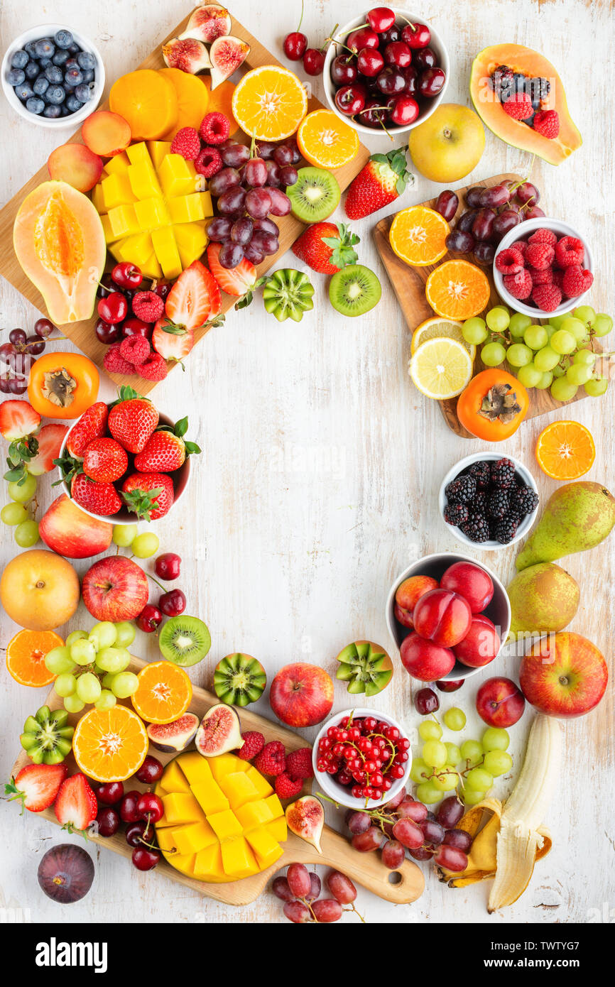 Healthy cut fruits frame, strawberries raspberries oranges plums apples kiwis grapes blueberries mango persimmon, on white table, copy space, top view - Stock Image
