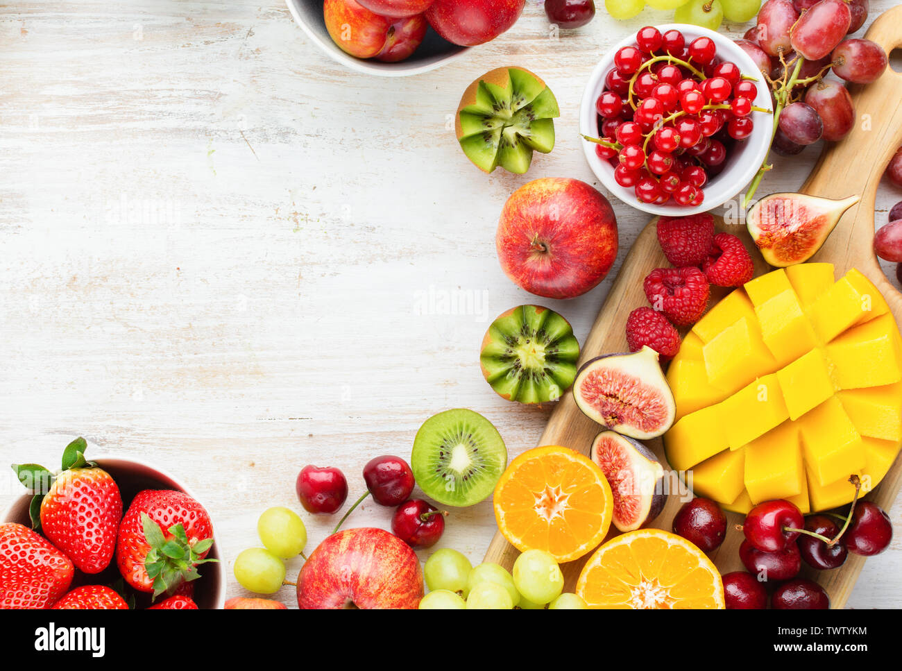 Colorful fruits background, cut mango, strawberries raspberries oranges plums apples kiwis grapes blueberries cherries, on white table, copy space, to - Stock Image