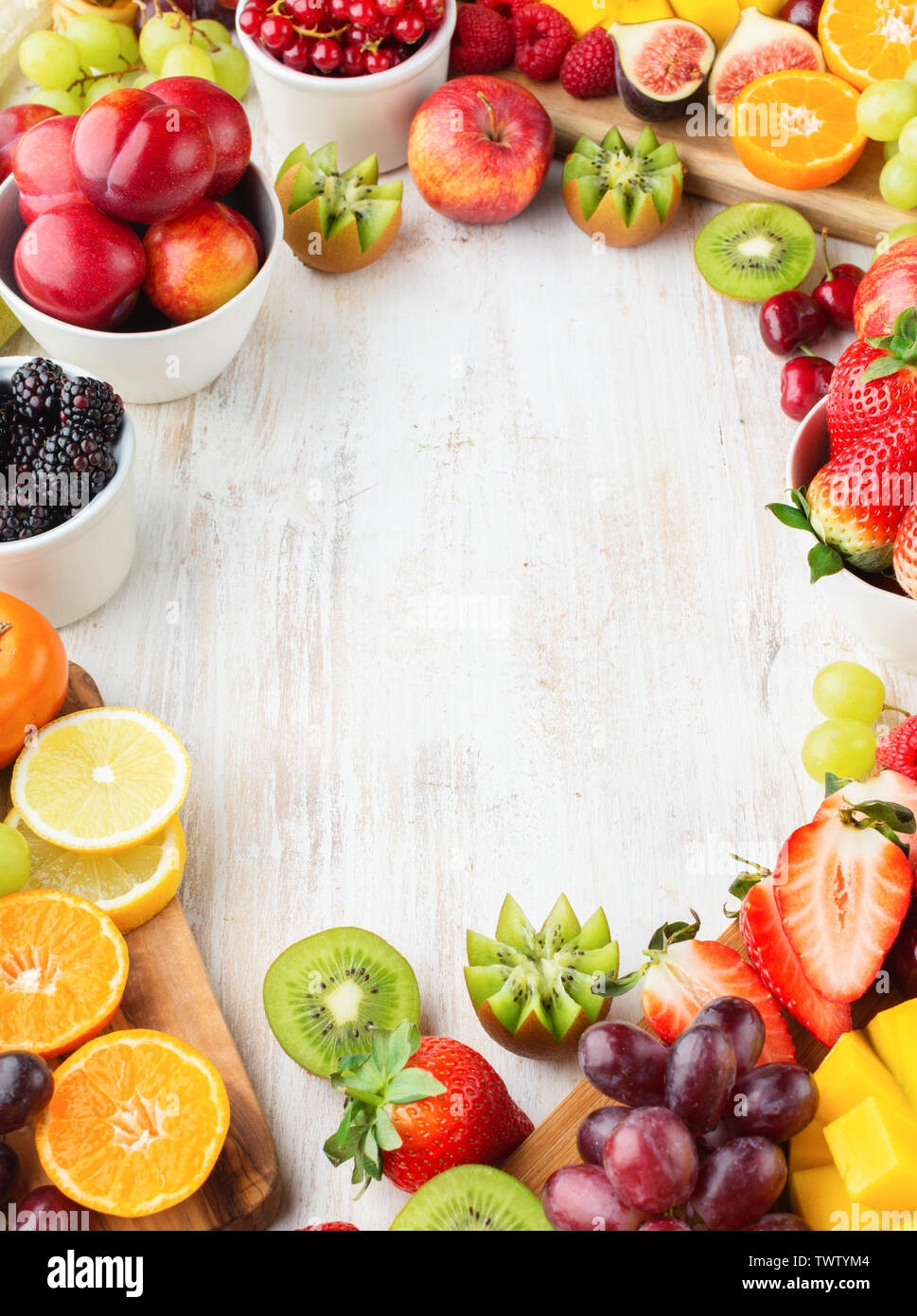 Healthy raw background, cut fruits, strawberries raspberries oranges plums apples kiwis grapes blueberries mango persimmon, on white table, copy space - Stock Image