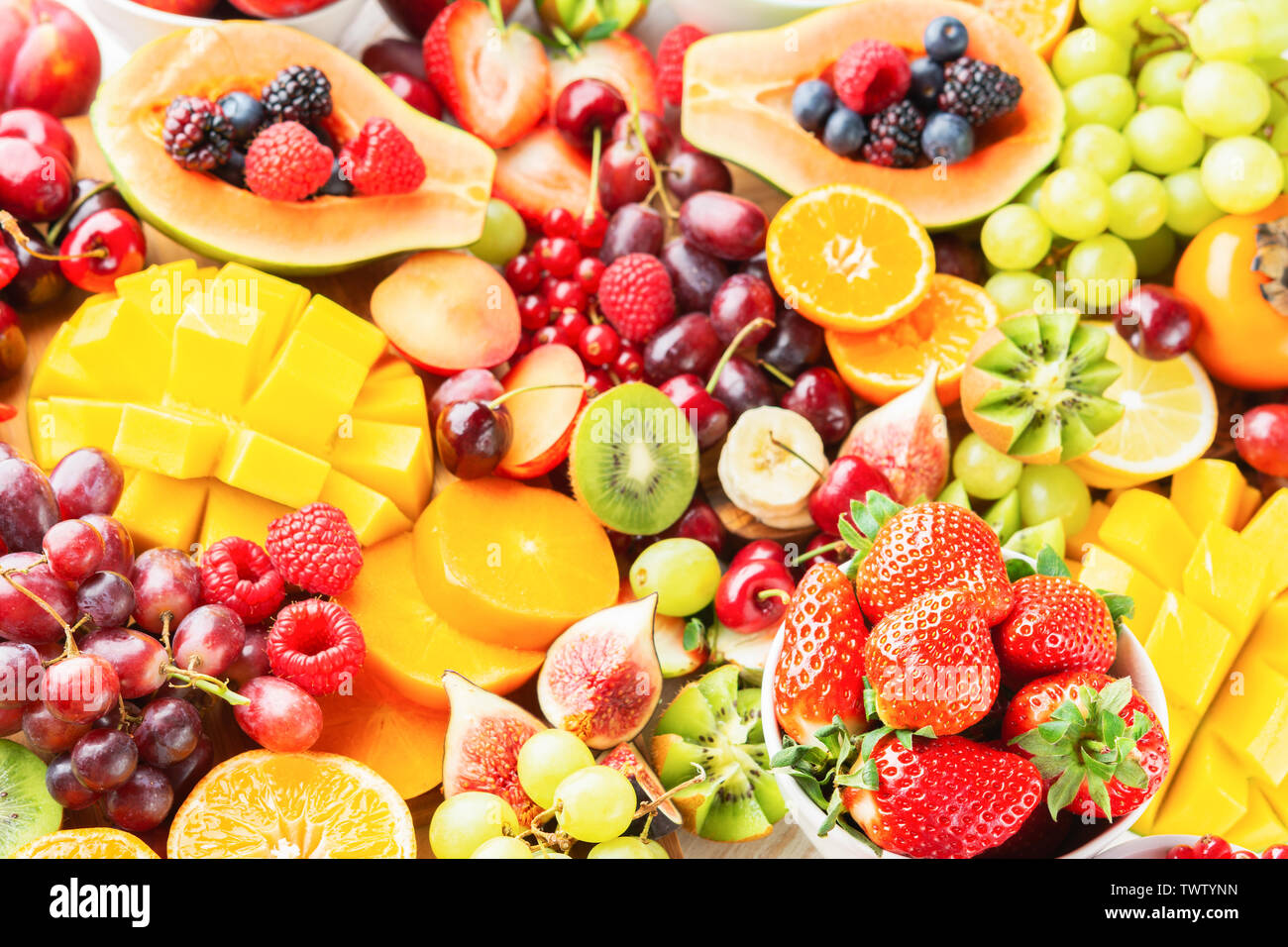 Raw cut fruit platter background, strawberries raspberries oranges plums apples kiwis grapes red currants blueberries mango persimmon, selective focus - Stock Image