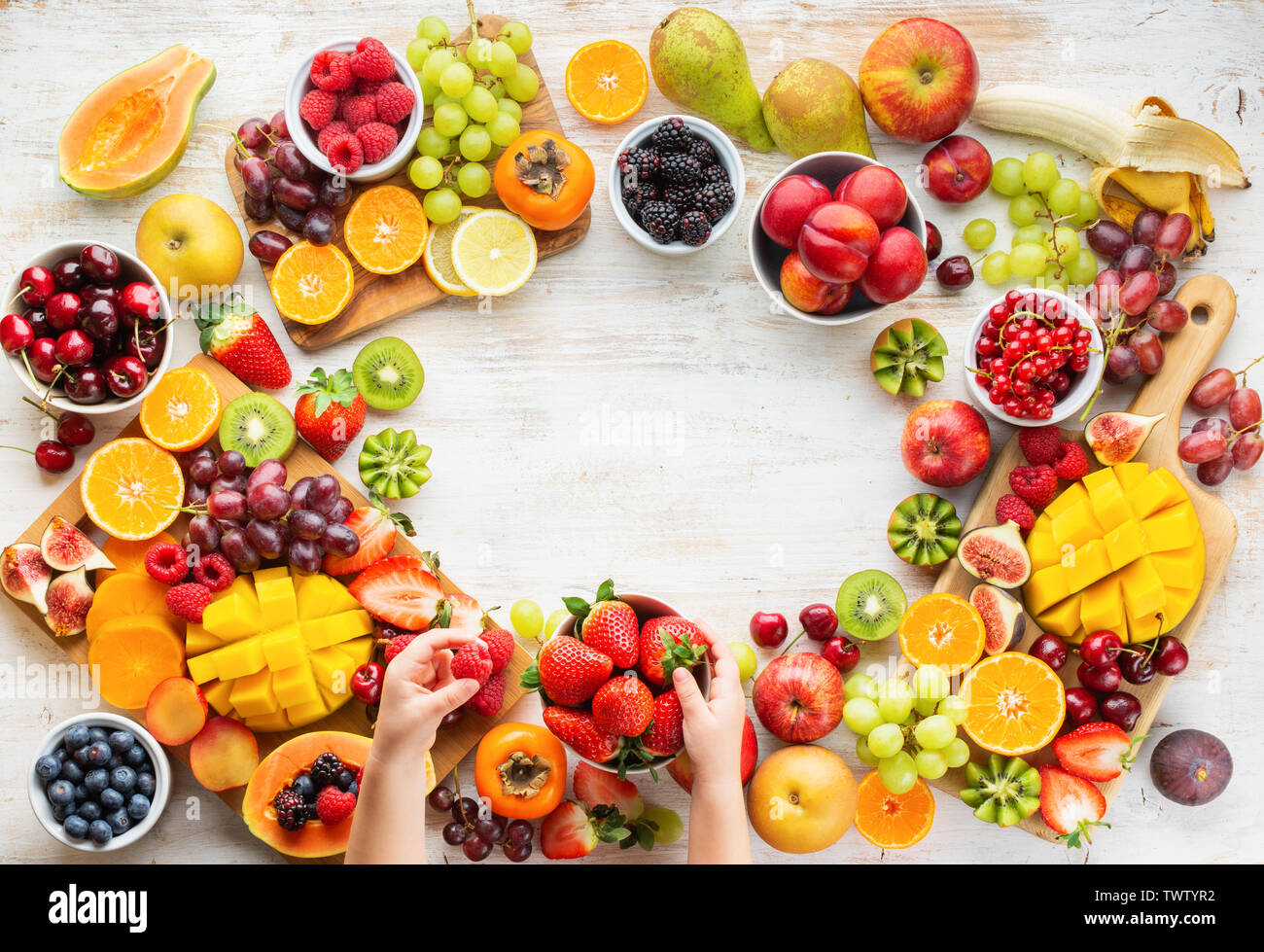 Raw healthy breakfast frame, cut fruits, strawberries raspberries oranges plums apples kiwis grapes blueberries mango on white table, child's hands ho - Stock Image