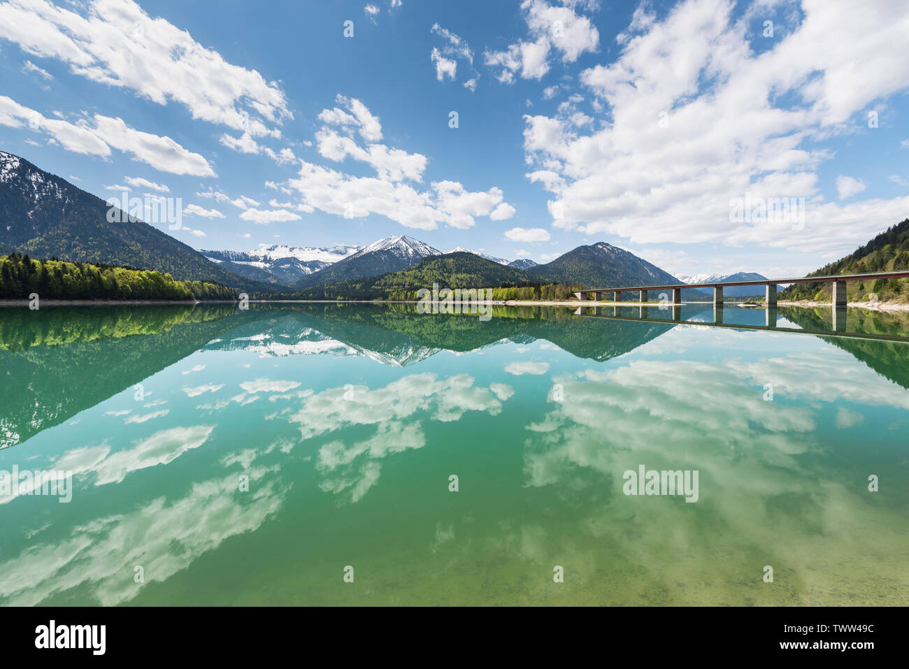 Blue sky with white clouds over the Sylvenstein reservoir in front of snowy mountains of the Karwendel with reflections in turquoise water, Bavaria - Stock Image