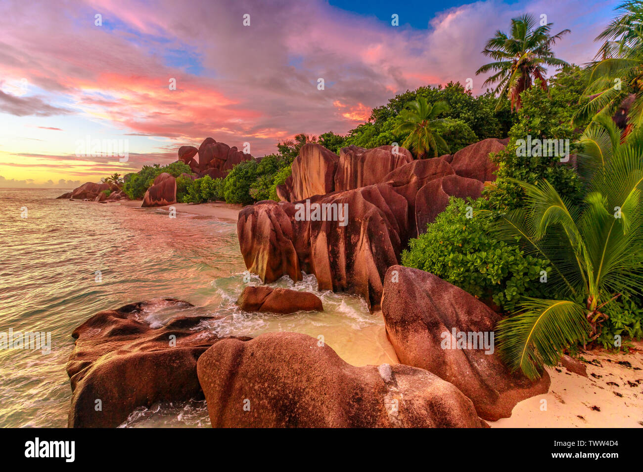 Dramatic colorful sky at twilight at scenic Anse Source d'Argent Beach in Seychelles, La Digue. Aerial view of amazing landscape with huge shaped rock - Stock Image