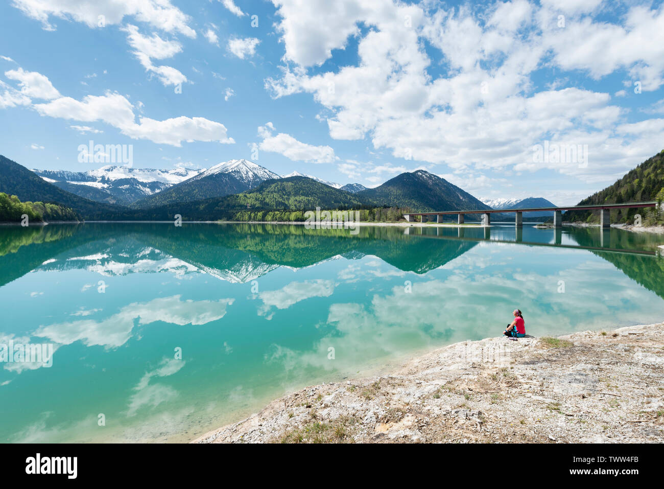 Woman sitting on the shore of the Sylvenstein reservoir and looking at the Karwendel mountains reflected in the turquoise water, Bavaria, Germany - Stock Image