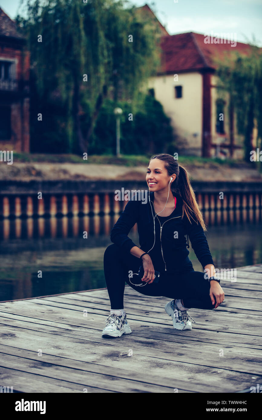 Attractive female runner taking break after jogging  by the river. Listening to music and using smart phone. - Stock Image