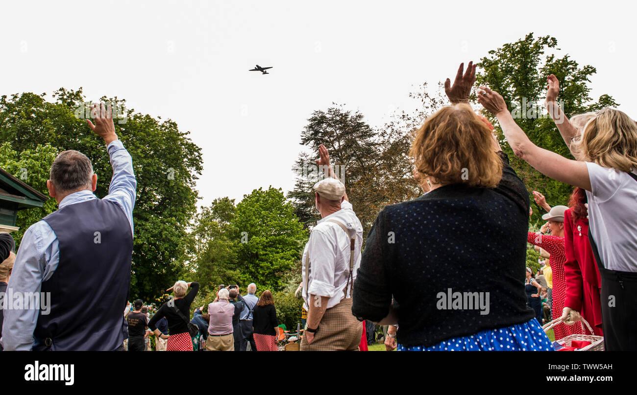 People waving as Dakota aeroplane flies past in the Valley Gardens on 1940s Day, Harrogate, England, UK, 23rd June 2019. Stock Photo
