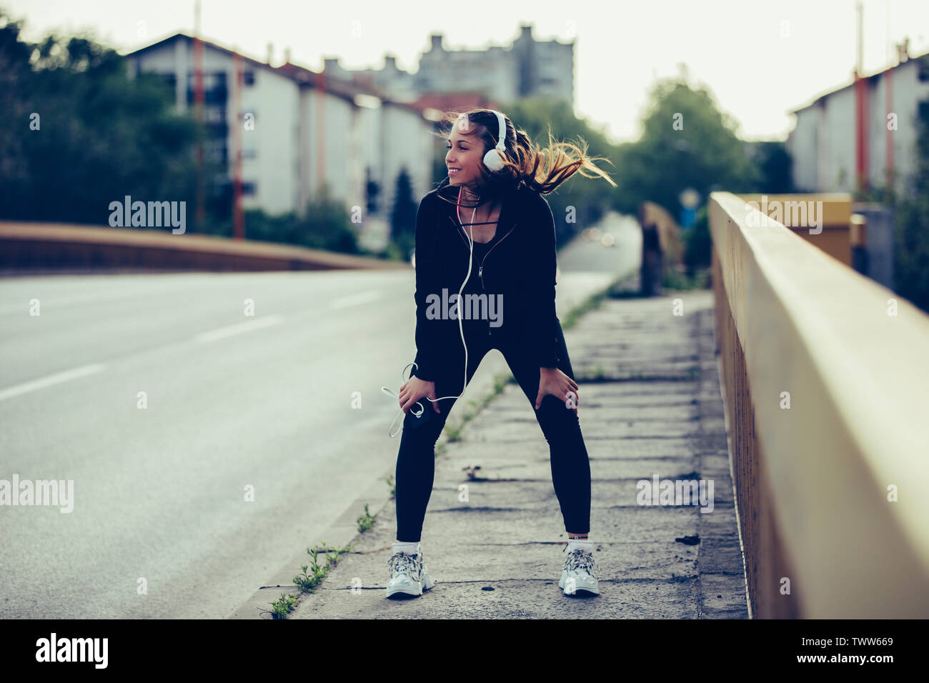 Young woman in black sports outfit resting while listening to music after running on the bridge in the city. - Stock Image