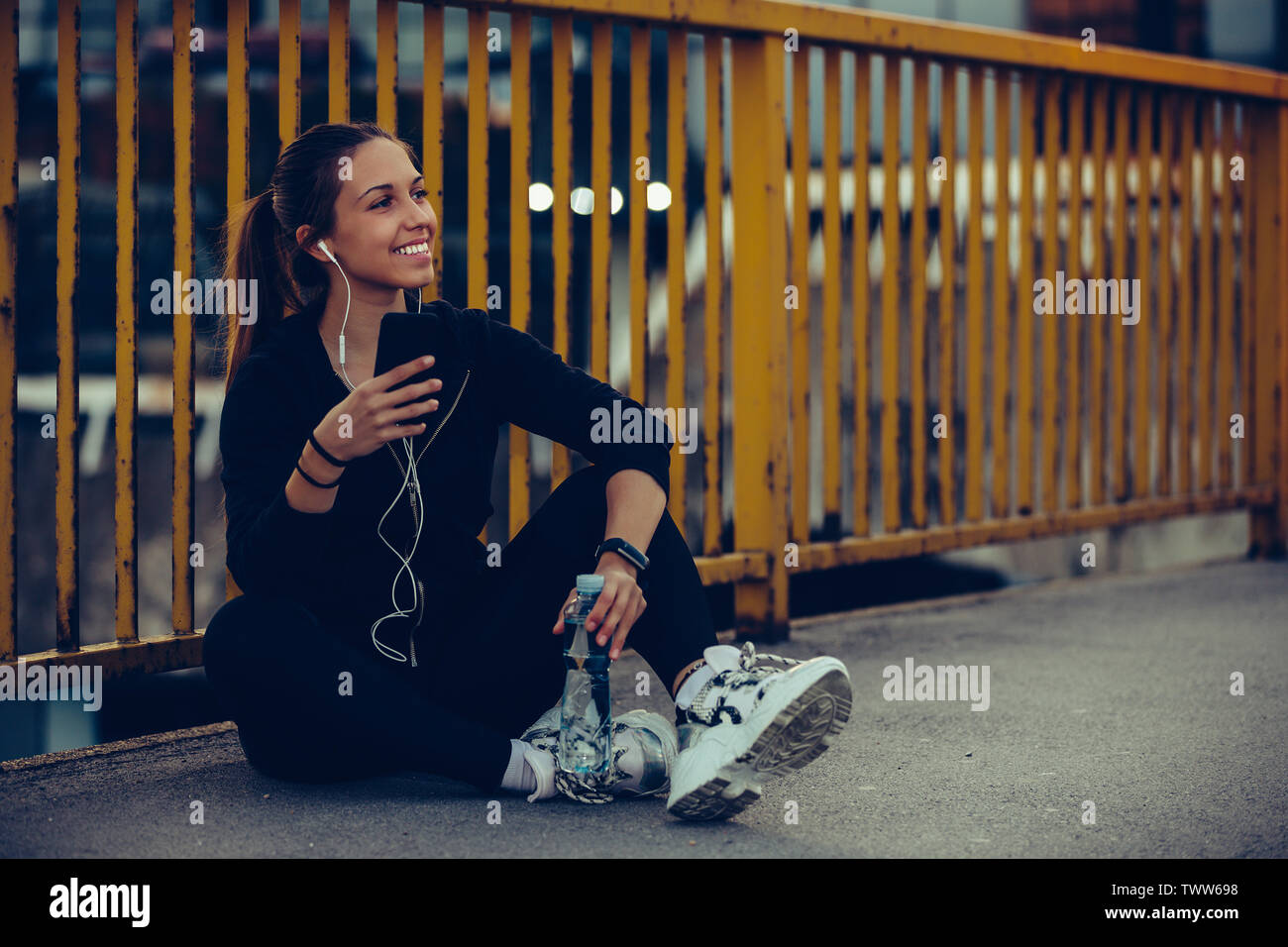 Young woman in black sports outfit resting while listening to music on her smartphone after running on the bridge, at night. - Stock Image