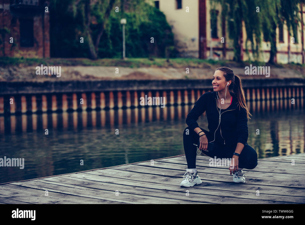 Attractive young woman taking break after jogging  by the river. Listening to music and using smart phone. - Stock Image