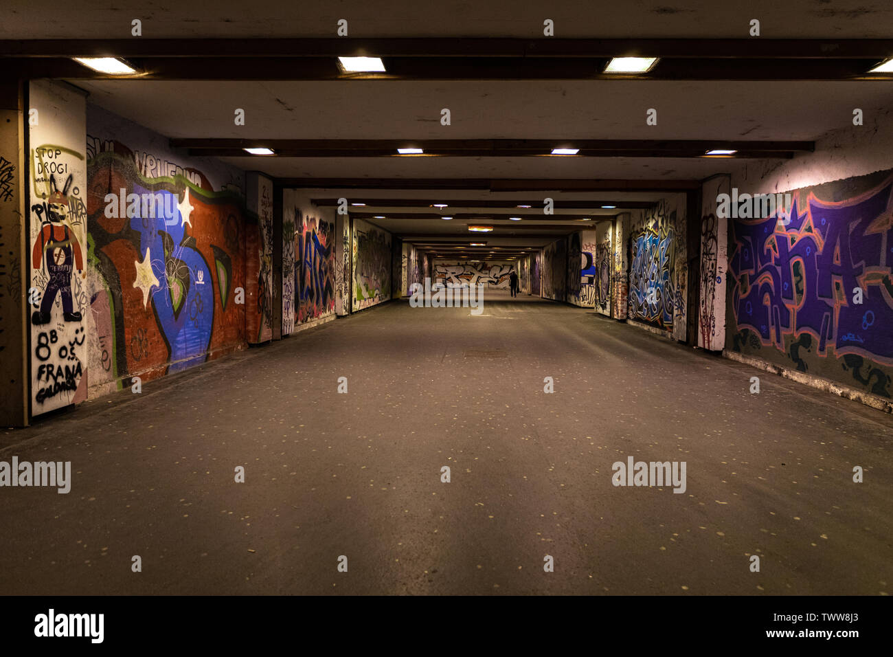 Croatia, Zagreb, June 21, the dark passage of a deserted, eerie creepy concrete indoor urban pathway grafted with graffiti at night - Stock Image