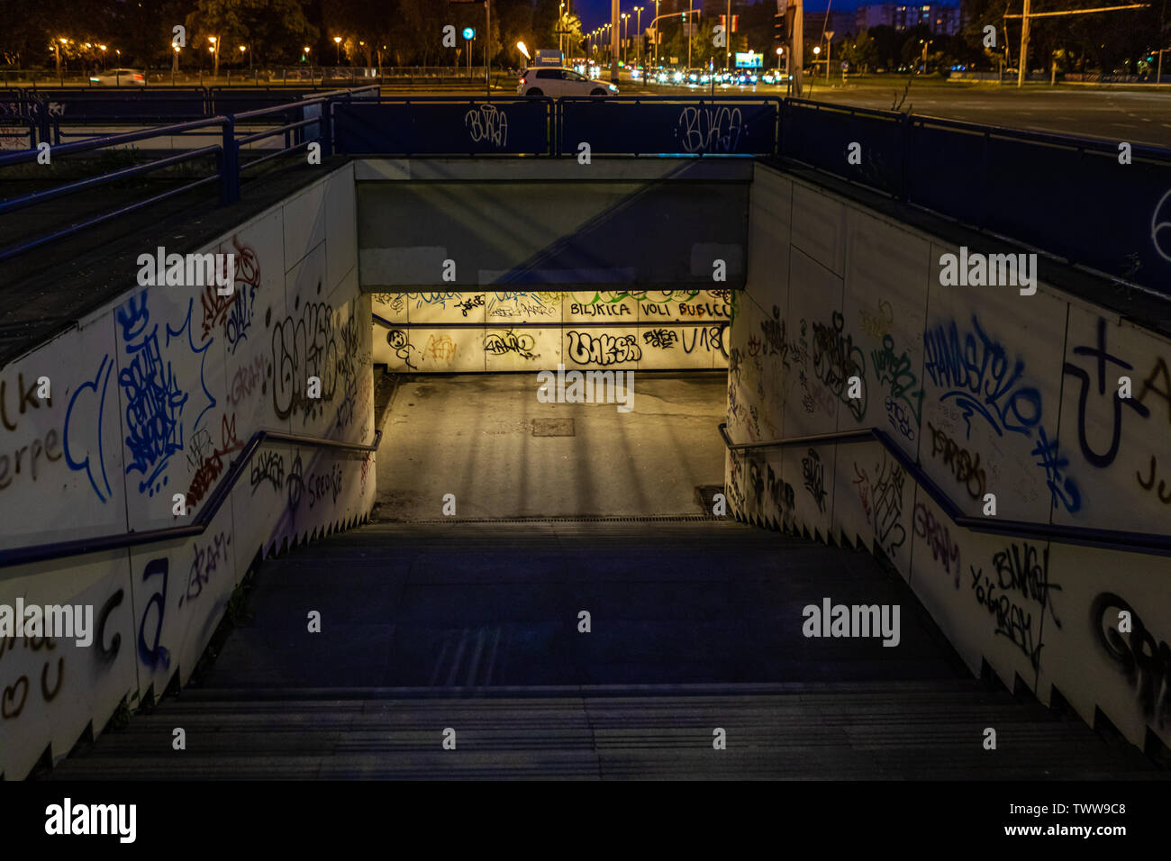 Croatia, Zagreb, June 21, the dark passage of a deserted, eerie creepy concrete indoor urban pathway grafted with graffiti at night Stock Photo