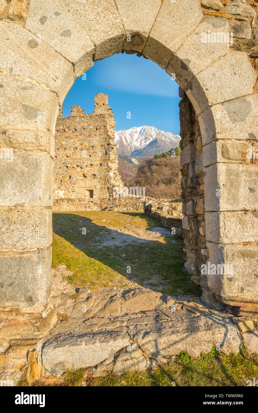 Snowcapped mountains view through stone arch, medieval castle ruins in Cimbergo, Val Camonica. Old fortress in the mountains of Italy. Stock Photo