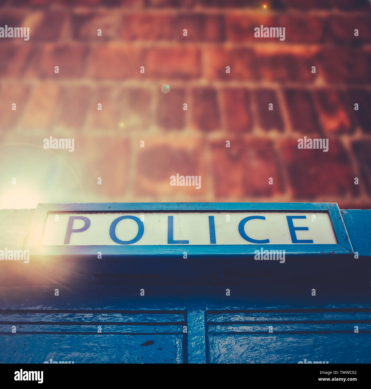 British Police Box With Lens Flare Against A Red Brick Wall With Copy Space Stock Photo