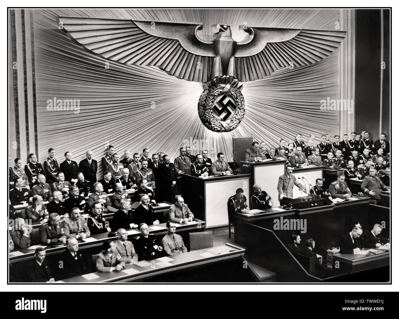 Adolf Hitler PODIUM REICHSTAG SPEECH Vintage pre-war 1930's German Nazi Propaganda Image of German Chancellor Adolf Hitler (standing at lectern) delivering a speech at the Reichstag on the 'Jewish question,' threatening the annihilation of European Jewry should another war break out, 30 January 1939. Adolf Hitler – Führer and Reich Chancellor of Germany and Leader of the Nazi Party Germany Stock Photo