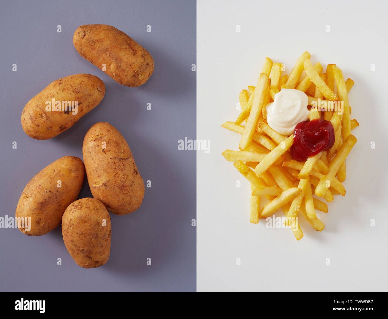 Several whole potatoes and pile of fries with ketchup on top over two tone pink and purple background - Stock Image