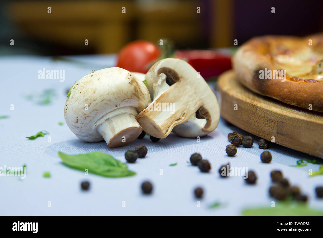 Raw mushrooms in a bowl on the table bunch dill and parsley . White mushrooms champignons, dill, parsley, old wooden table, rustic style, selective fo - Stock Image