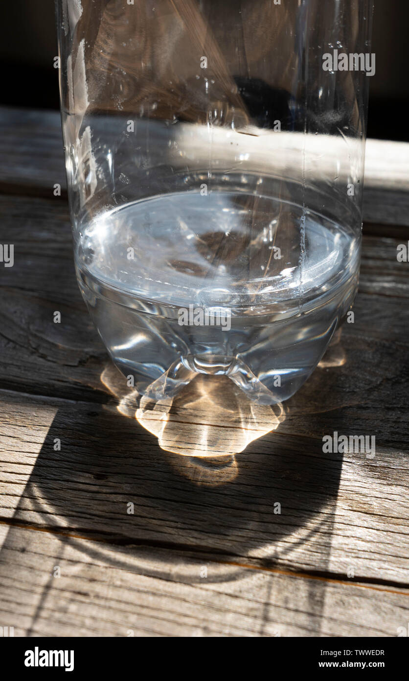 a plastic bottle half full of water on a wooden table - Stock Image
