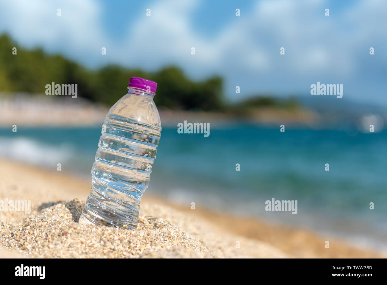 Bottle of cold fresh water on beach sand. Summer concept - Stock Image