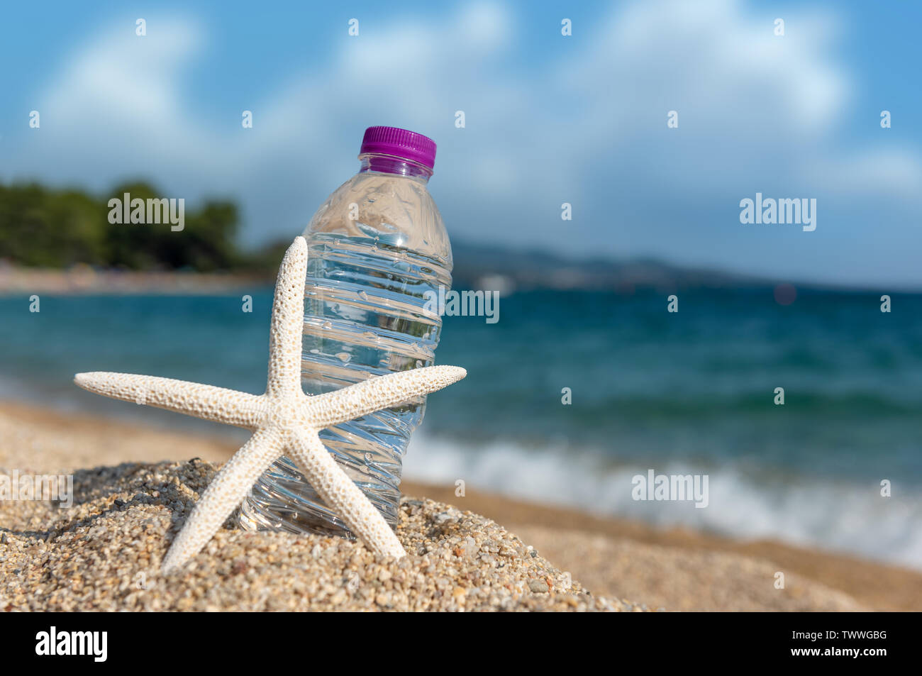 Bottle of cold fresh water with starfish on beach sand. Summer concept - Stock Image